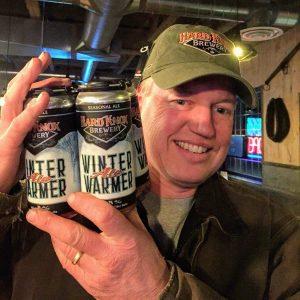Hard Knox Brewery Man Posing Beside 4 Case of Fresh Winter Warmer Ale Craft Beer