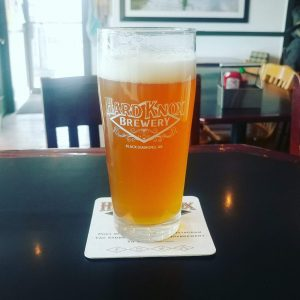 Hard Knox Brewery Freshly Filled Pint Glass Sits on Coaster On Table Top