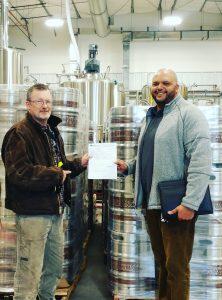 Hard Knox Brewery Photo of Two Men Posing in Front of Freshly Filled Craft Beer Kegs