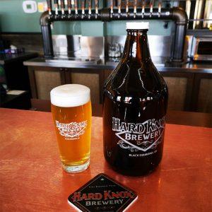 Hard Knox Brewery Growler Sits Next to Freshly Filled Pint of Hard Knox Beer