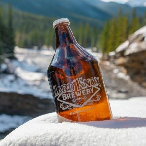 Hard Knox Brewery Refillable Glass Growler Sitting in Snow with Mountainous Background