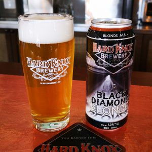 Hard Knox Brewery's Own Black Diamond Blonde Tall Boy Sit Atop Light Countertop Next to Freshly Filled Pint Glass