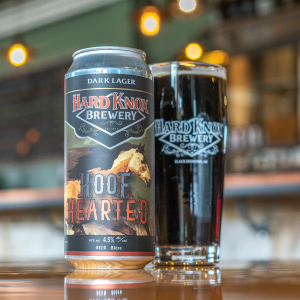 Hard Knox Brewery Hoof Hearted Dark Lager Can Sits Atop of Countertop Next to a Freshly Filled Pint Glass