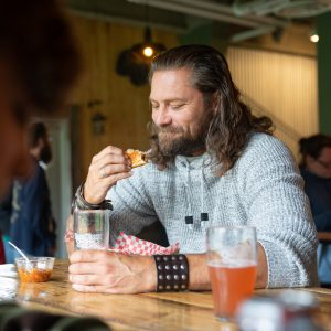 Man Enjoys Pint of Hard Knox Brewery Craft Beer Paired with His Food Selection of Choice Inside Hard Knox Brewery Taproom