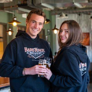 Male Wearing Black Hard Knox Brewery Hoodie Poses Beside Female Wearing Identical Hoodie Inside Hard Knox Brewery Taproom