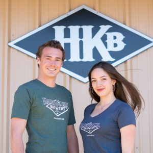 Male Wearing Green HKB T-Shirt Poses Beside Female Showcasing Blue HKB T-Shirt in Front of Hard Knox Brewery Taproom