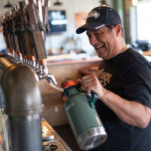 Cheerful Man Laughs as He Fills Hard Knox Brewery Growler at Hard Knox Brewery Taproom in Black Diamond Alberta