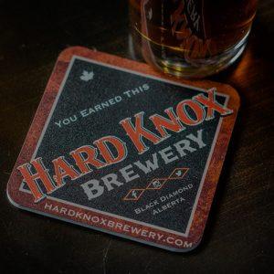 Hard Knox Brewery Beer Sits Atop Countertop Next to Hard Knox Brewery Coaster
