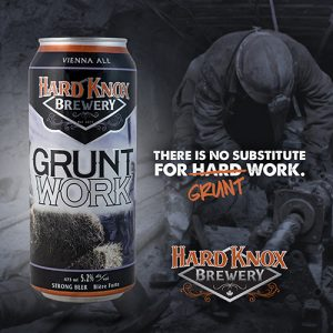 Hard Knox Brewery Grunt Work Vienna Ale is Shown in Foreground as Iron Worker Performs Intensive Labour Using Necessary Equipment in Background
