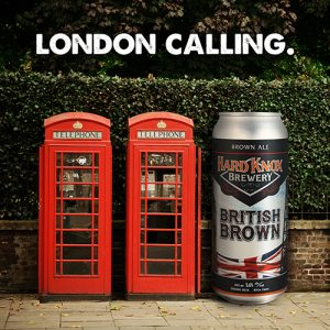 Hard Knox Brewery British Brown Ale is Shown Beside Two Red British Pay-phones with Large Green Hedge in Background