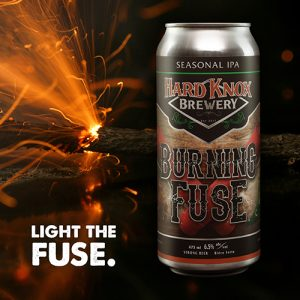 Hard Knox Brewery Burning Fuse Seasonal IPA is Showcased in Foreground as Lit Fuse Burns in Background