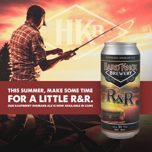 Hard Knox Brewery R&R Raspberry Rhubarb Ale is Showcased in Foreground as Man Casts Fishing Rod in Background