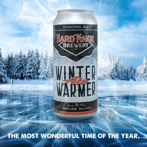 Hard Knox Brewery Winter Warmer Seasonal Ale can sits Frosted Atop of Frozen Pond with Snow in Background