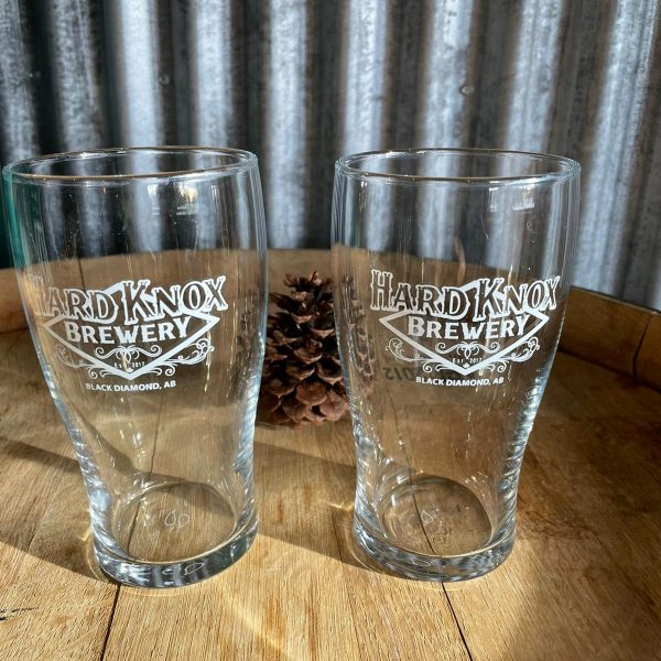 Two Hard Knox Brewery Pint Glasses Sitting on top of Wooden Table with Acorn in Background